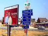 Serbia - Kosovo - Bank billboard and direction boards by the road - photo by J.Kaman