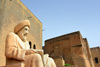 Erbil / Hewler / Arbil / Irbil, Kurdistan, Iraq: statue of the historian Ibn Al-Mustawfi aka Mubarak Ben Ahmed Sharaf-Aldin and red brick buildings near the entrance to Erbil Citadel - Qelay Hewlêr - UNESCO world heritage site - photo by M.Torres