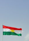 Erbil / Hewler, Kurdistan, Iraq: flag of Kurdistan against blue sky - Zoroastrian inspired sun disk and red, white and green stripes, no crescent... - photo by M.Torres
