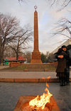 Bishkek, Kyrgyzstan: fire and love - couple at the Red Guards Memorial - Oak Park - red granite obelisk - grave of the Bolshevik casualties of the 1918 Belovodsk uprising - eternal flame - photo by M.Torres