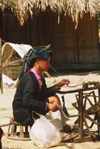 Laos: in a typical Laos village a woman is handspinning wool - spinning wheel - worsted - photo by E.Petitalot