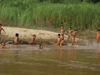 Laos - Mekong River: kids enjoying the river on the muddy waters - photo by M.Samper