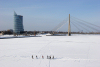 Latvia / Latvija / Lettland - Riga: frozen Daugava - crossing the river - Saules Akmens building and Vansu bridge in the background - walking on the ice - photo by Alex Dnieprowsky