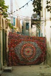 Libya - Tripoli: carpet hanging to close off street for private family celebration (photo by G.Frysinger)