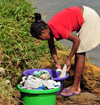 Soanierana Ivongo, Analanjirofo, Toamasina Province, Madagascar: woman washing clothes by the river - photo by M.Torres