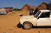 Tsimafana, Belo sur Tsiribihina district, Menabe Region, Toliara Province, Madagascar: huts and battered Peugeot 504 pickup -  European Car of the Year in 1969 - photo by M.Torres