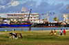 Toamasina / Tamatave, Madagascar: the port seen from blvd Ratsimilaho - freighter MSC Trader and cows grazing - photo by M.Torres