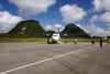 Mulu Airport, Sarawak, Borneo, Malaysia: MASwings Fokker F50 twin turboprop on the tarmac at MZV, gateway to Gunung Mulu National Park - 9M-MGB cn 20156 - karstic hills covered in vegetation in the background - photo by A.Ferrari
