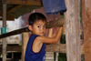 Skandis, Lubok Antu District, Sarawak, Borneo, Malaysia: young Iban boy, inside the longhouse - photo by A.Ferrari