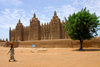 Djenné, Mopti Region, Mali: woman walking in front of Great Mosque of Djenné - UNESCO world heritage site - architect Ismaila Traoré - Grande mosquée de Djenné - photo by J.Pemberton