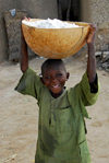 Djenn�, Mopti Region, Mali: boy carrying a flour container on his head - photo by J.Pemberton