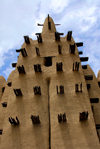 Djenné cercle, Mopti Region, Mali: tower of a mud brick Mosque in a village outside Djenne - deleb palm wood embedded in the adobe walls serves as scaffolding for repairs - Sahel Islamic architecture - photo by J.Pemberton