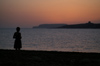 Malta - Comino: sunset - island silhouette seen from Marfa point in Malta - girl on the beach (photo by A.Ferrari)