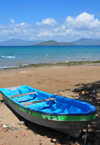 Pamandzi, Petite-Terre, Mayotte: beach - boat with M'Bouzi islet and Mahor� island in the background - photo by M.Torres
