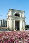 Chisinau / Kishinev, Moldova: Arc de Triomphe - victory of the Russian Army over the Turks - Cathedral park - Parcul Catredalei - architect I. Zaushkevich - background: Government House - Arca Triumfala 'Portile Sfinte' - Pita Marii Adunari Nationale - photo by M.Torres