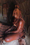 Namibia: Himba Woman sitting in hut, Skeleton Coast, Kunene region - photo by B.Cain