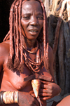 Namibia: Himba Woman Smearing ochre on herself, Skeleton Coast, Kunene region - photo by B.Cain