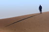 Namibia: Man on sand dune casting long morning shadow, Skeleton Coast - photo by B.Cain