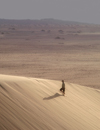 Namibia: Man walking on sand dune, Skeleton Coast - photo by B.Cain