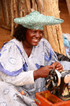 Kunene region, Namibia: Herero woman making souvenier dolls - Namibian hat - sewing machine - photo by Sandia