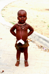 Kunene region, Namibia: Himba boy - travelling in the country with his mother - photo by Sandia