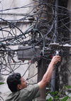 Kathmandu, Nepal: an electrician working in Katmandou street - chaotic wires - photo by E.Petitalot