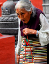 Kathmandu, Nepal: an old Tibetan woman recites prayers around a Buddhist temple - photo by E.Petitalot