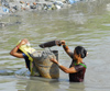 Kathmandu, Nepal: women extract back sand in a polluted river - photo by E.Petitalot