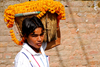 Kathmandu, Nepal: Pashupatinath Temple - man carrying a basket of marigolds - photo by J.Pemberton