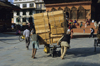 Kathmandu, Nepal: day labourers push a large load - Durbar square - photo by W.Allg�wer