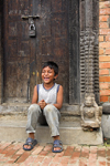 Patan, Lalitpur District, Bagmati Zone, Nepal: local boy sitting in carved doorway - photo by J.Pemberton