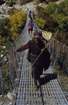 Annapurna area, Nepal: woman with bamboo basket crossing a suspension bridge - photo by W.Allgöwer