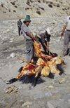 Annapurna area, Nepal: men cutting a slaughtered yak - photo by W.Allgöwer