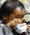Nepal - Langtang region - young child eating rice in a bowl - photo by E.Petitalot