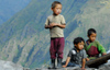 Nepal - Langtang region - poor children on a roof, looking down, mountains of Langtang national park in the background - photo by E.Petitalot