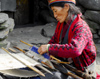 Nepal - Langtang region - old woman weaving a carpet - photo by E.Petitalot