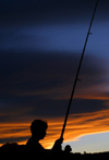 New Zealand - silhouette of a man fishing (photographer: Mark Duffy)
