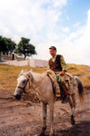 Nagorno Karabakh - Dirimbon: rough rider - cowboy, Caucasus style - war memorial in the background (photo by M.Torres)
