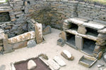 Orkney island - Skara Brae - View of House #1 - from right to left are the stone dresser where prizeobjects were stored and displayed, a box bed, lower center is the hearth,and in front of the dresser are containers for preparing fish bait - photo by Carlton McEachern