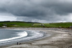 Orkney island - Skara Brae- beach - two boys play in the sand oblivious to the waves and storm rollingin - photo by Carlton McEachern