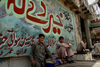 Peshawar, NWFP, Pakistan: mural and idle men - photo by G.Koelman