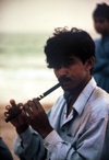 Karachi, Sindh, Pakistan: musical evening - man playing the flute on the beach - photo by R.Zafar