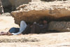 Karachi, Sindh, Pakistan: men resting under rocks - while waiting for customers at the French Beach - the shade - photo by R.Zafar