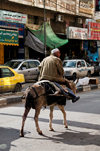 Hebron, West Bank, Palestine: man rides a donkey in street - photo by J.Pemberton