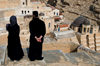Mar Saba Monastery, West Bank, Palestine:  Greek Orthodox monk and female visitor overlooking the monastery - Great Lavra of St. Sabas - photo by J.Pemberton