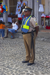A Panamanian policeman watches the crowd at Devils and Congos festival, Portobello, Colón, Panama, Central America - photo by H.Olarte