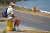 Panama City: an American tourist takes a roadside rest in Panama's Amador Causeway - photo by H.Olarte