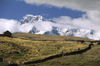 Ausangate massif, Cuzco region, Peru: hikers cross a farm on the high Altiplano below the mighty Andean peak of Ausangate - Peruvian Andes - Cordillera Blanca - photo by C.Lovell