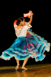 Lima, Peru: young woman dancer turning on a stage in Lima - Peruvian ethnic clothing with a flowing blue skirt and pink handkerchief - photo by D.Smith
