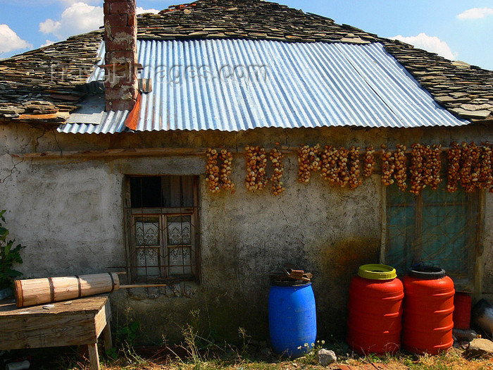 albania161: Kamnik, Kolonjë, Korçë county, Albania: rural house with onion braids and half stone half metal roof - photo by J.Kaman - (c) Travel-Images.com - Stock Photography agency - Image Bank
